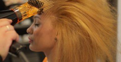 mujer alisando cabello con Los 6 Mejores Secadores de Pelo con Alisador